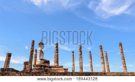 Ancient Buddha statue sitting posture among the ruins pillars under the blue sky at Wat Maha That temple in Sukhothai Historical Park is an old city and famous attractions Thailand 16:9 wide screen