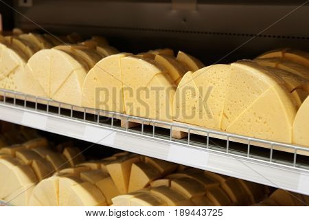 Sold by weight plain cheap cheese on supermarket shelf