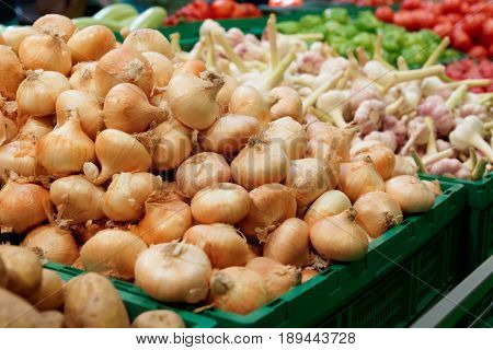 Shelf with onion and garlic in supermarket