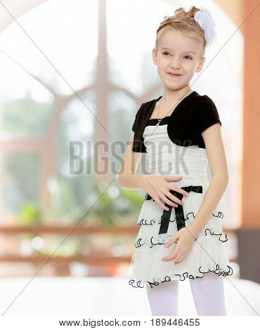 Beautiful little blonde girl dressed in a white short dress with black sleeves and a black belt.Girl poses for the camera.In a room with a large semi-circular window.