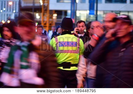 CARDIFF UK - 3 JUNE 2017 Policeman standing amongst fans during Champions League Final. British police and security services on high alert as hundreds of thousands of fans enjoy football in the capital of Wales