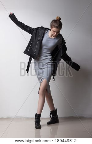 Young beautiful fashion model posing over white wall. Rock and punk style. Stylish dress and jeans.