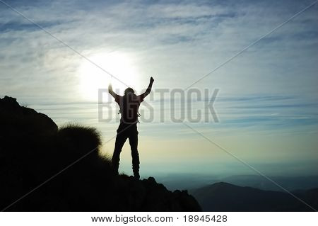 Trekker silhouette at the summit of his climb