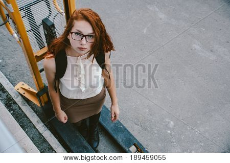 A girl in light clothes and red hair stands on a hydraulic stackers. Industry people. Art.