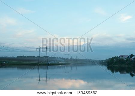 Evening misty landscape of the countryside. The river is in a fog. Wires of electric voltage.
