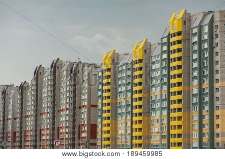 Modern multi-storey apartment buildings are built in a row. Multi-family houses of different colors.