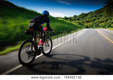 Motion blur of cyclist in maximum effort in a road outdoors