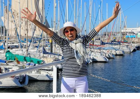 A middle-aged woman in a good mood dressed in a navy style have fun in the background of the bay with yachts