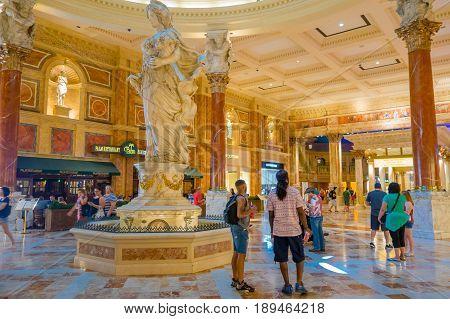 LAS VEGAS, NV - NOVEMBER 21, 2016: An unidentified people walking in the interior of Venetian Hotel in Las Vegas watching a beautiful statue of a greek woman.