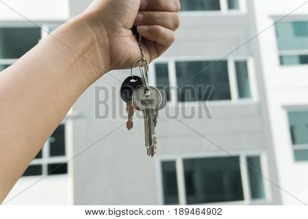 A Hand Is Holding A Key From The New Condominium High Rise Condominium Buildings Background.