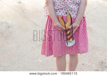 Girl holding a slingshot in her hands