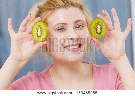 Woman Having Gel Mask On Face Holding Kiwi