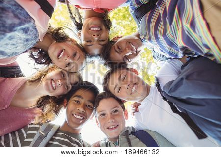 Portrait of smiling school kids forming a huddle in campus at school