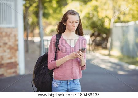 School girl with schoolbag using mobile phone in campus at school
