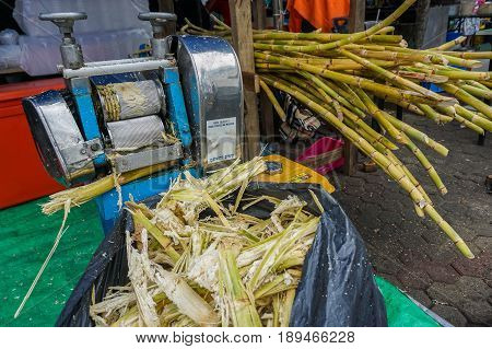 Kota Kinabalu,Sabah-May 28,2017:Sugar cane juice with cut pieces cane ready to crush sugar cane machine & making the juice in Kota Kinabalu,Sabah,Malaysia.Its an extremely common street drink in Asean
