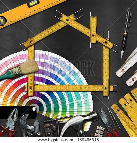 Home improvement concept - Yellow wooden ruler in the shape of a house on a blackboard with work tools