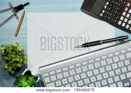 Top view of an office desk with a computer keyboard pencil calculator drawing compass and an empty sheet of paper with copy space