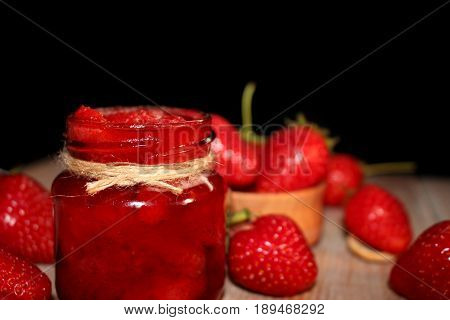 beautiful red strawberries and strawberry jam are on the wooden docks