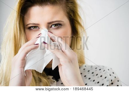 Woman Being Sick Having Flu Sneeze Into Tissue