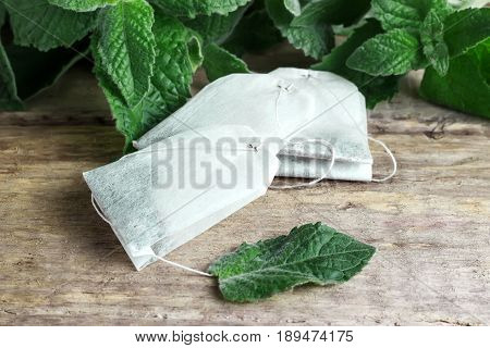 Three packets of tea on a mint background on a wooden background
