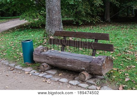 Wooden bench made of tree trunk in the park