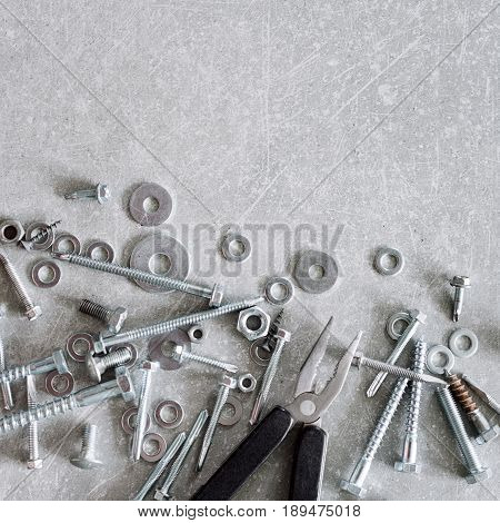 Construction tools. The screws, nuts and bolts with pliers on concrete background. Repair, home improvement concept. Free space for text, top view, flat lay