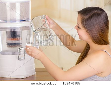 Beautiful woman holding a glass of water in one hand and a pitcher of water in her other hand, with a filter system of water purifier on a kitchen background.