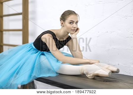 Beautiful ballerina sits on the wooden table on the textured white wall background in the studio. She wears a black leotard with a cyan tutu and pointe shoes. She looks into the camera. Horizontal.