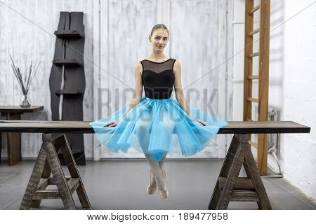 Smiling ballerina sits with crossed legs on the wooden table on a light wall background in a studio. She wears a black leotard with a cyan tutu and pointe shoes. She looks into the camera. Horizontal.