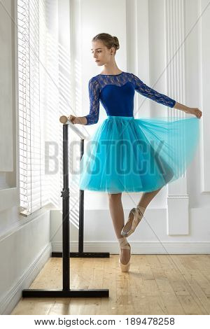 Wonderful ballerina stands on the right toe next to the ballet barre on the white wall background. She wears a lace blue leotard, cyan tutu, pointe shoes and looks to the side. Indoors.