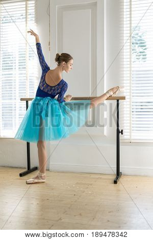 Attractive ballerina stands next to the ballet barre and holds right leg and hand on it on the white wall and windows background. She wears a lace blue leotard, cyan tutu, pointe shoes. Indoors.