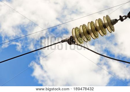Glass electrical power insulator taken close up against of blue cloudy sky.