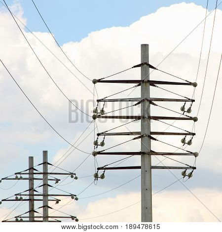 Electric Power Transmission Lines and Electricity Towers on cloudy sky background.