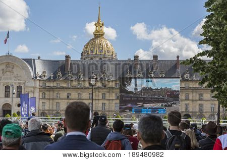 PARIS - 20 May 2017: Spectators in front of the Dome des Invalides watch on a big screen the formula e cars during the 2017 Paris ePrix. These cars are electric-powered.