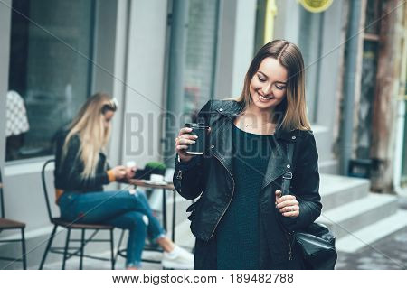 Beautiful young stylish casual woman wear in fashion clothes and staying on street and holding black cup of coffee, enjoying, smiling and look at cam. Lifestyle, fashion, street style concept.