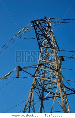 The support of the high-voltage transmission line against the blue sky
