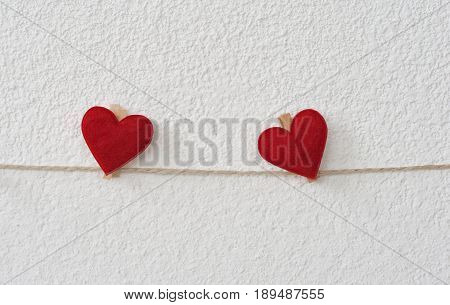 Two hearts with clothes pegs on a cord on structure plaster