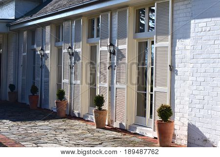 old homestead with french doors and vintage lamps opening on to courtyard with shrubs in terracotta pots