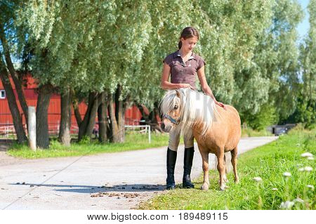 Friendship and trusting. Smiling teenage girl standing and stroking cute little shetland pony. Summertime outdoors image.