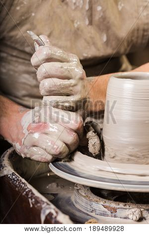 pottery, workshop, ceramics art concept - male master sculpts with a utensil with sponge and carving tools, man hands work with potter's wheel, fingers form shape of raw clay, vertical