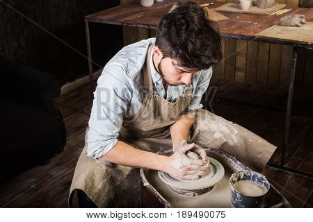 pottery, workshop, ceramics art concept - man working on potter's wheel with raw clay with hands, a male brunette sculpt a utensils near wooden table with tools, master in apron and a shirt, top view