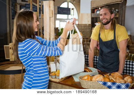 Smiling female customer receiving a parcel from staff at counter in bakery shop