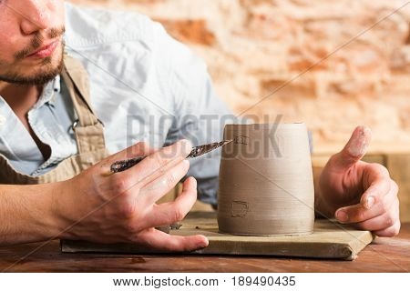 pottery, stoneware, ceramics art concept - closeup on craftsman bent over a clay cup with tool, macro of male hands connecting pieces of fireclay, young male sits at a workshop behind the table