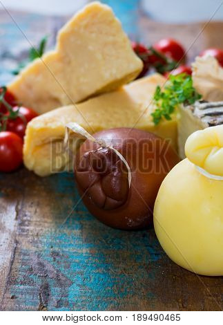 Traditional Italian hard cheeses Parmesan Grana Padano Pecorino Caciocavallo Provolone on wooden plate