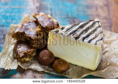 Ancient french cheese Tomme de Montagne and dried figs with figs bread on wooden background