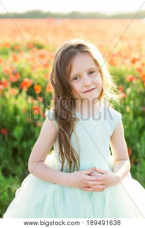 beauty, childcare, happiness, behaviour, health concept - portrait of charming light-skinned girl, wearing alice blue sleeveless dress, folding her tender hands and smiling