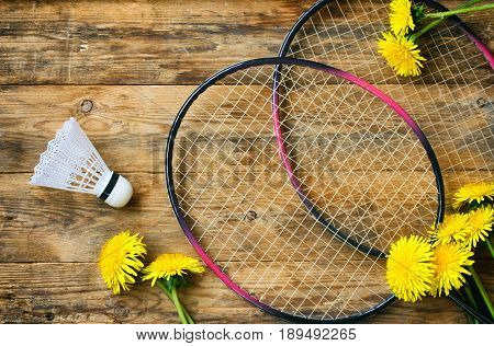 Two rackets of badminton and shuttlecock on a wooden table dandelions summer sport vacation concept