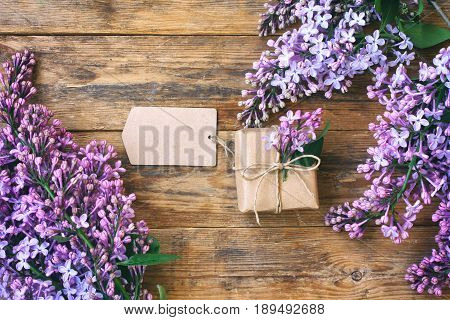 Branches of a blossoming violet lilac wrapped gift box blank paper tag on an old wooden table top view