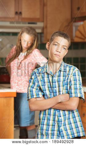 Mother Stands With Hands On Hips In Kitchen Behind Frustrated Son