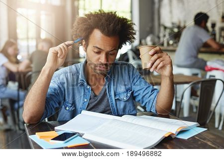 Concentrated Thoughtful Black European Student With Afro Hairstyle Scratching Head With Pen, Drinkin